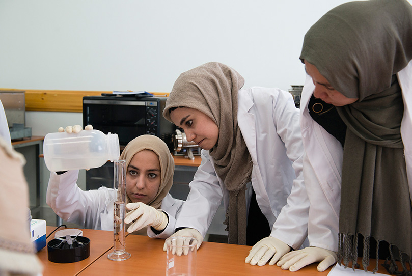Three female students filling a test tube inside the food technology lab at Herat University