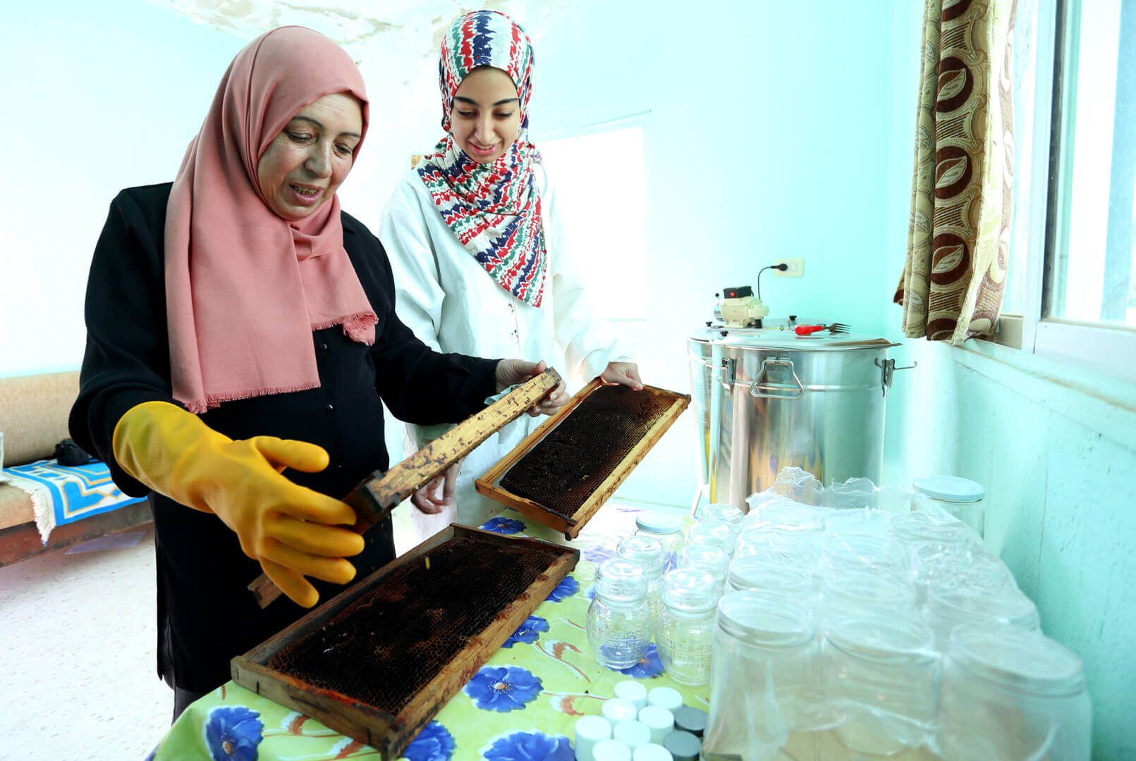 Samira Saeed Mouawwad working with a female mentee to make honey