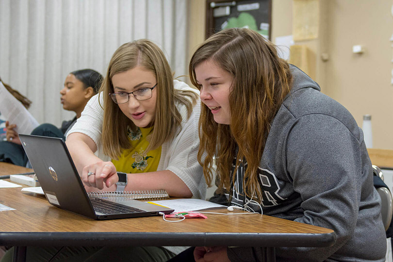A teacher and a student looking at a laptop computer