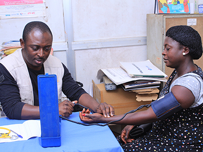 man taking woman's blood pressure in health clinic