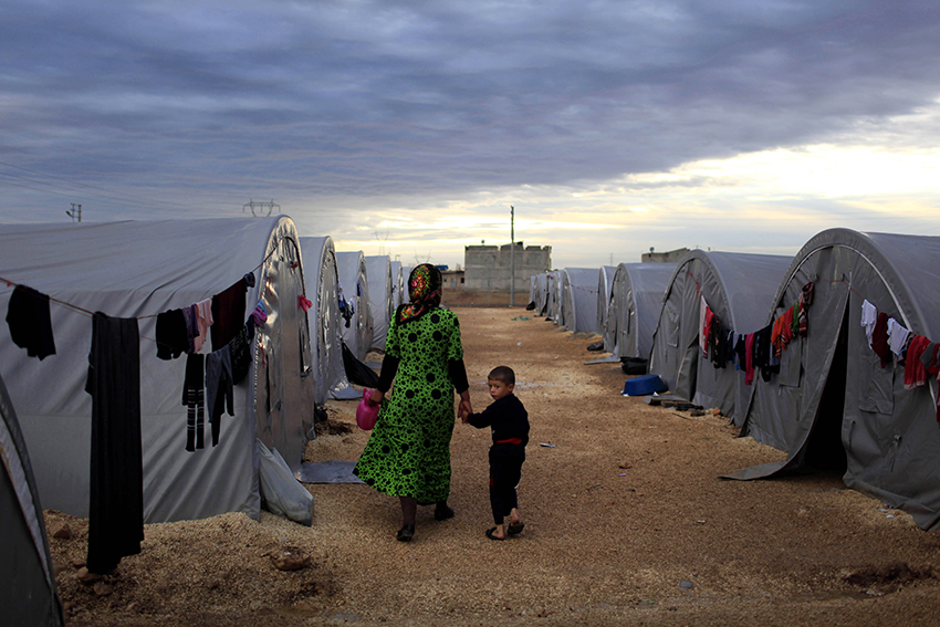Woman in headscarf walking between refugee camp holding boy's hand
