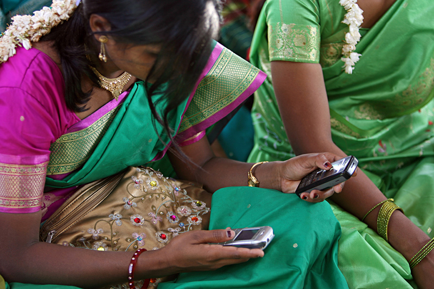 Young women look at their cellphone during a community meeting