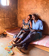 Photo caption: A farm couple relaxes on a mattress in their hut in the war-weary Gulu District of Northern Uganda.