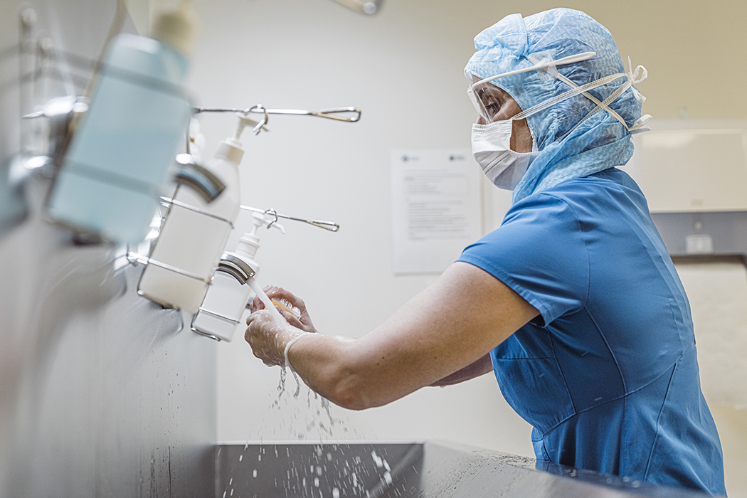 medical worker wearing protective equipment washing hands