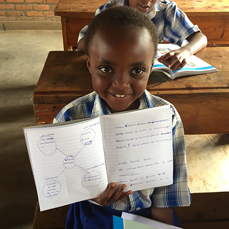 young student smiling showing off his notebook