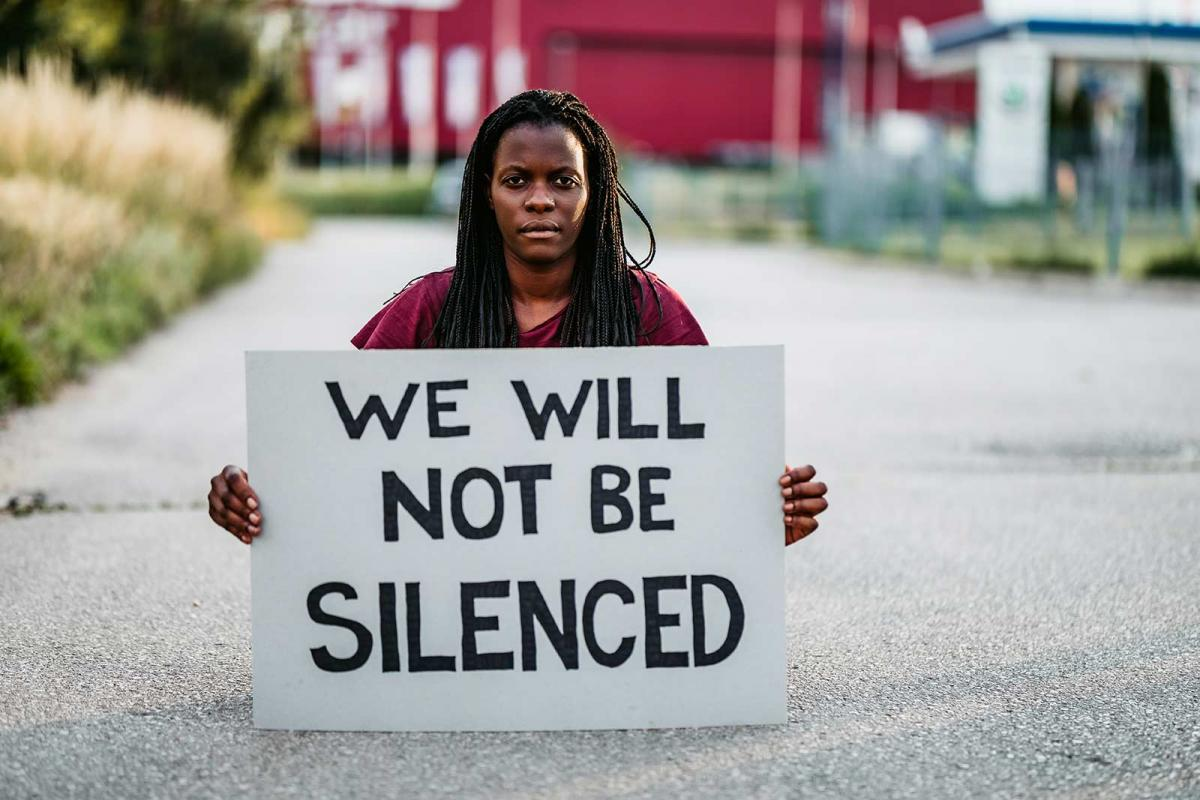 Woman holding a handmade sign that says 'We will not be silenced'