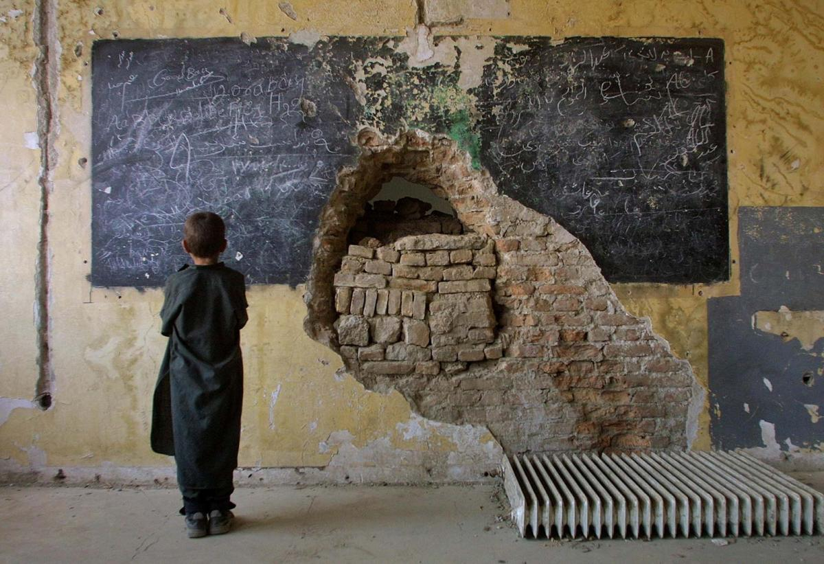 Boy looking at chalkboard in destroyed classroom