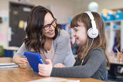 teacher with student in classroom using technology
