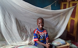 All smiles in front of a bed net donated by the Malaria Action Program for States (MAPS) project to students in Oyo state.