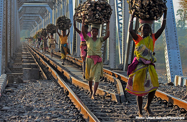 women carrying wood on train tracks