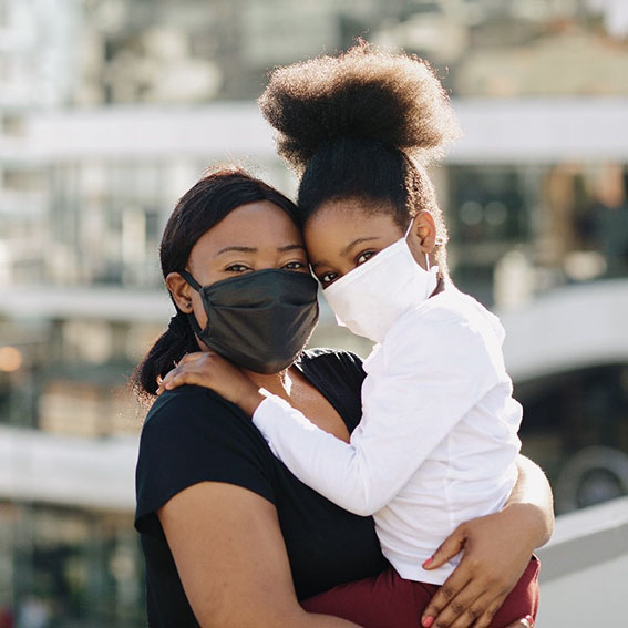 woman holding daughter both wearing masks