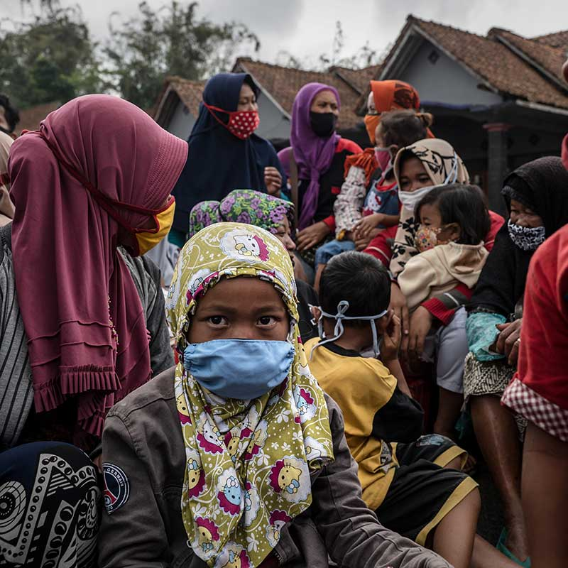 Group of children and women wearing masks in Southeast Asia