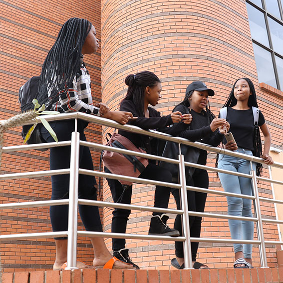 female students chatting outside school holding onto railing.