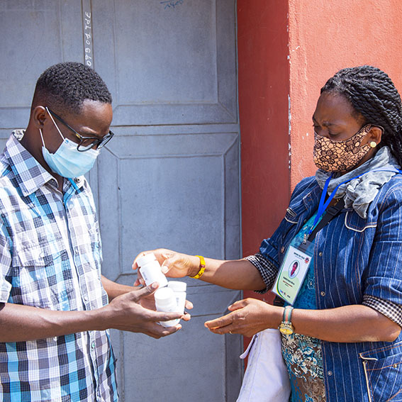 Healthcare worker hands medication to a man