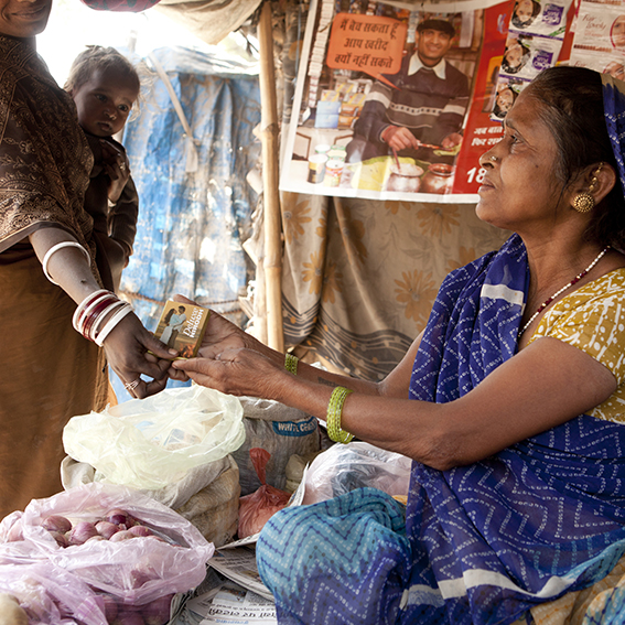 woman paying woman for goods at market