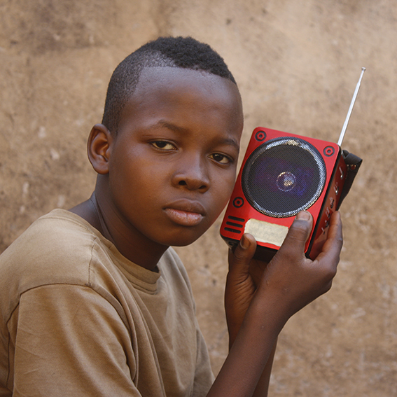 young boy holding radio up to ear