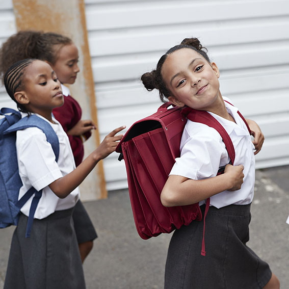 young girl students confidently walking to school