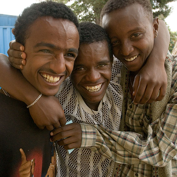 3 young men hugging and smiling
