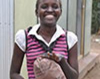 school girl holds sanitary pad provided through FHI 360 project