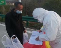 man wearing mask receiving instructions from medical personnel