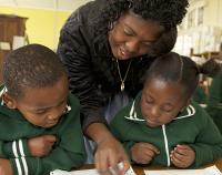 teacher assisting students counting coins