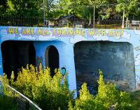 """bridge with art painted that says """"We are all thriving with HIV!"""""""