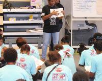 Female standing teaching students sitting on floor