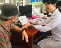 nurse helps man understand blood pressure screening by showing chart