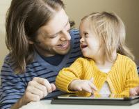 Man with young girl using tablet