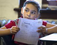 girl in school at desk reading notes