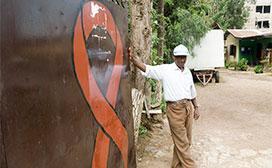 man next to large AIDS ribbon