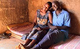 A farm couple relaxes on a mattress in their hut in the war-weary Gulu District of Northern Uganda.