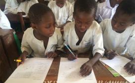 boys writing at desk