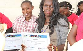 Hadija Abdi and Lorna Awuor receive their graduation certificate from Digital Opportunity Trust's entrepreneurship training program.