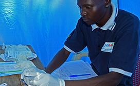Jimmy Sirari, an adherence support counselor at the Malaba Model Health Center, conducts an outreach activity. The CB-HIPP project piloted health units within existing health facilities to provide services for mobile populations in East Africa.