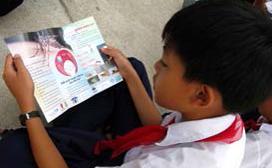 boy reading pamphlet