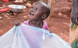 Kewina holds a mosquito net her brother received at school in Tanzania.