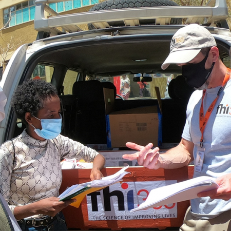Maereg, a health care provider, works with FHI 360 Technical Director for Tigray, Michael O'Brien, to review medical supplies provided to the internally displaced persons camp where she lives.