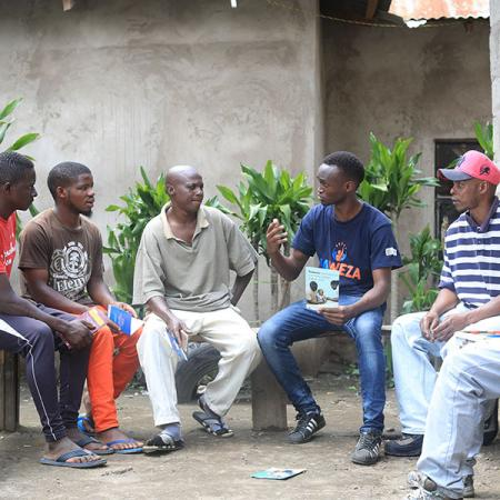 A USAID Tulonge Afya volunteer conducts a small group session with youth in Tanzania.