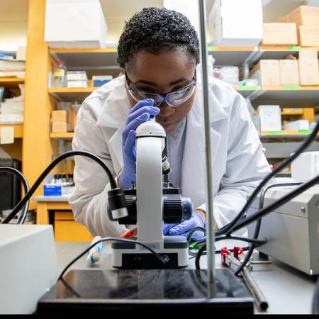 woman using microscope in lab